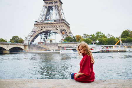 Young woman with long blond curly hair in Paris, France. Beautiful tourist in red coat near the Eiffel tower, on the Seine embankment Banque d'images
