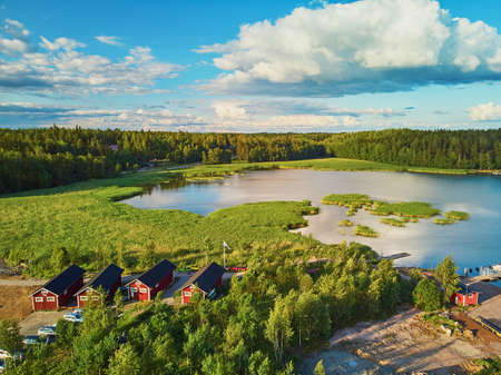 Scenic aerial view of colorful boats near wooden berth and buildings in the countryside of Finland at sunset 스톡 콘텐츠 - 138474348