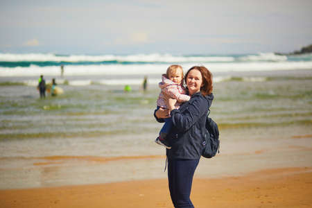 Mother and daughter enjoying Atlantic ocean on the beach. Woman holding little girl and showing her the sea. Tourists on La Concha beach in San Sebastian (Donostia), Spain