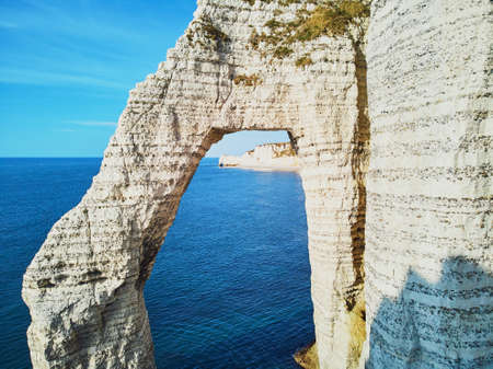 Picturesque panoramic landscape of white chalk cliffs and natural arches of Etretat, Seine-Maritime department of Normandy in France 免版税图像