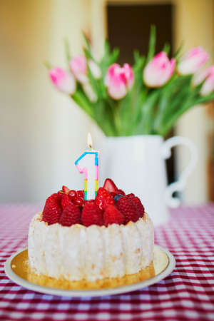 Delicious fruit cake with raspberries and candle in form of number one with bunch of beautiful pink tulipes in vase. Baby's very first birthday concept Imagens