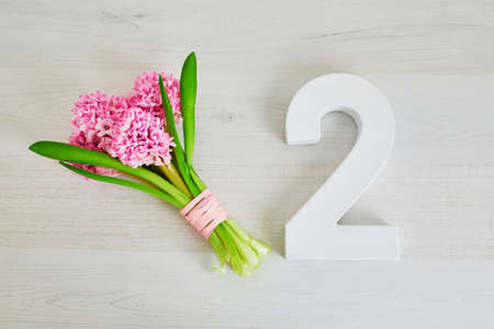 Bunch of pink hyacinths and white wooden number two. Second birthday or anniversary concept Banque d'images