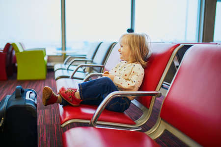 Adorable little toddler girl traveling by plane. Child sitting in gate and waiting for the flight. Traveling abroad with kids. Unaccompanied minor concept