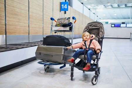 Adorable little toddler girl in international airport. Small child sitting in pushchair near heavy luggage. Traveling abroad with kids