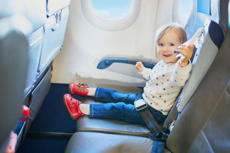 Adorable little toddler girl traveling by plane. Small child sitting by aircraft window and playing with toy aircraft during the flight. Traveling abroad with kids. Unaccompanied minor concept