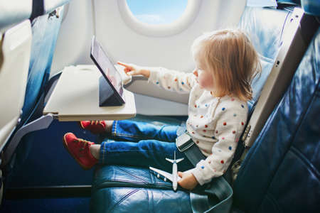 Adorable little toddler girl traveling by plane. Small child sitting by aircraft window and using a digital tablet during the flight. Traveling abroad with kids. Unaccompanied minor concept