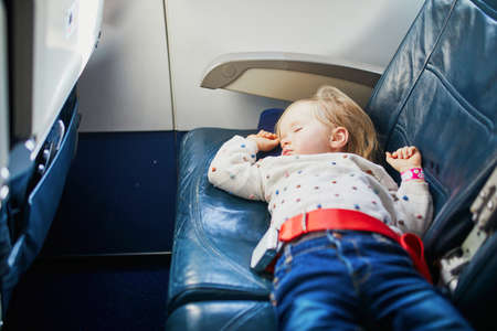 Adorable little toddler girl traveling by plane. Small child lying on a seat and sleeping during the flight. Traveling abroad with kids. Unaccompanied minor concept