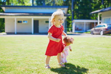 Adorable baby girl in red dress playing with a doll outdoors on a sunny summer day. Little child having fun. Kid playing stuffed toys Imagens