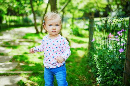 Adorable petite fille marchant dans un parc verdoyant un jour d'été. Petit enfant s'amusant à l'extérieur. Enfant explorant la nature