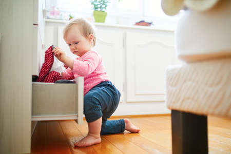 Adorable toddler girl at home, opening the drawer of dresser and taking out clothes. Curious little kid exploring her flat or house. Home child proofing concept