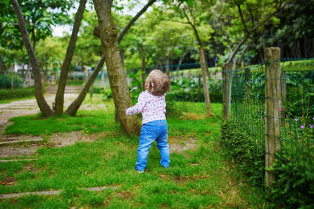 Adorable toddler girl walking in green park on a summer day. Little child having fun outdoors. Kid exploring nature