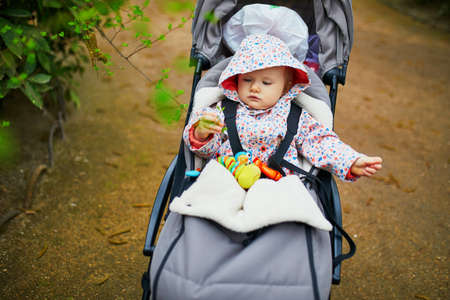 Adorable baby girl sitting in stroller and looking at first green leaves on a spring day in park. Kids exploring nature