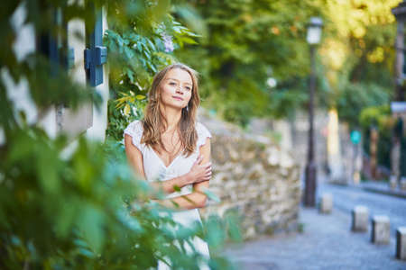 Beautiful young woman in white dress leaning against the wall on Montmartre hill in Paris, France at early morning