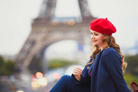 Young woman with long blond curly hair in Paris, France. Beautiful tourist in red beret near the Eiffel tower