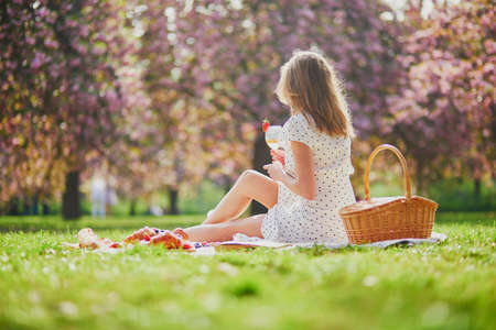 Beautiful young woman having picnic on sunny spring day in park during cherry blossom season