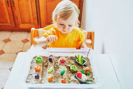 Little girl playing with toy fruits and vegetables and kinetic sand at home, in kindergaten or preschool. Child making a kitchen garden. Indoor creative games to entartain kids staying at home