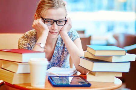 Student with tablet, books and papers, studying at home. Quarantine and closed schools and offices during coronavirus outbreak. Homeschooling, distance learning and freelance job 写真素材