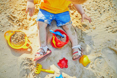 Adorable little girl on playground in sandpit. Toddler playing with sand molds and making mudpies. Outdoor creative activities for kids