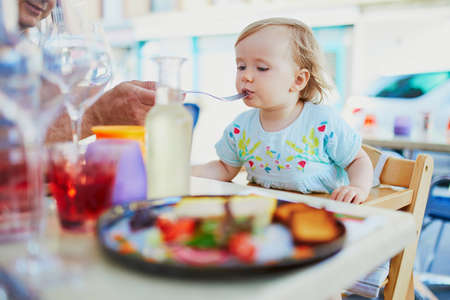 Adorable toddler girl sitting in high chair in cafe or restaurant. Father feeding his little daughter. Going out with kids concept Stock Photo