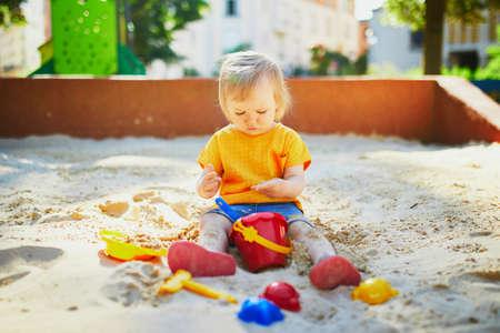 获得可爱的小女孩在沙坑的操场上乐趣。蹒跚学步的孩子玩沙模,做泥饼。儿童户外创意活动