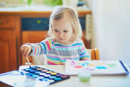 Adorable little girl painting with aquarelle at home, in kindergaten or preschool. Creative games for kids staying at home Foto de archivo
