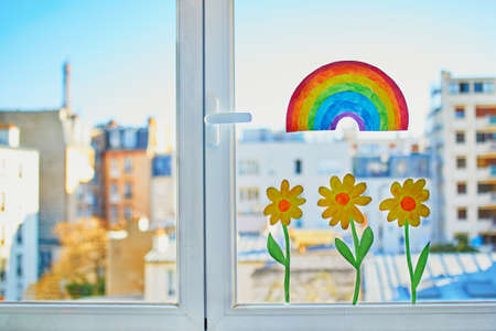 Colorful rainbow and yellow flowers painted on window glass in Parisian apartment, view to residential buildings with Eiffel tower in the background. Self isolation, social distancing and quarantine in Paris, France