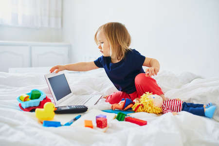 Toddler girl with laptop, notebook, phone and different toys in bed on clean white linens. Freelance, distance learning or work from home with kids concept Stock Photo