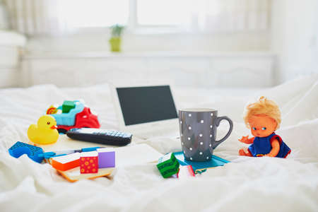 Laptop, cup of coffee, notebook, phone and different toys in bed on clean white linens. Freelance, distance learning or work from home with kids concept Stock Photo