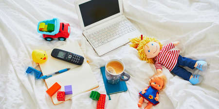 Laptop, cup of coffee, notebook, phone and different toys in bed on clean white linens. Freelance, distance learning or work from home with kids concept