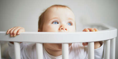 Adorable baby girl in co-sleeper crib attached to parents bed. Little kid sitting in cot
