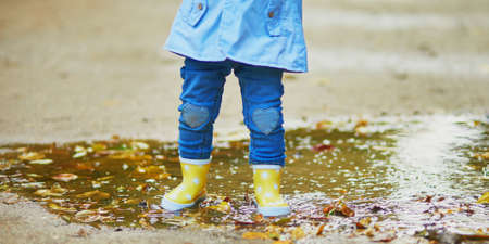 Child wearing yellow rain boots and jumping in puddle on a fall day. Toddler girl having fun with water and mud in park on a rainy day. Outdoor autumn activities for kids