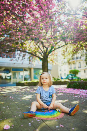 Adorable toddler girl drawing rainbow with colorful chalks on asphalt in park with blooming cherry blossom trees. Outdoor activity and creative games for small kids