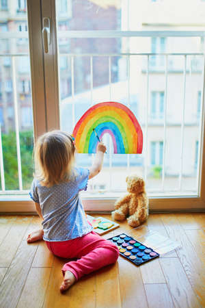 Adorable toddler girl painting rainbow on the window glass as sign of hope. Creative games for kids staying at home during lockdown. Self isolation and coronavirus quarantine concept Stock Photo