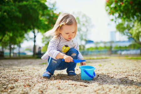 Adorable toddler girl playing with bucket and shovel, making mudpies and gathering small stones. Outdoor creative activities for kids