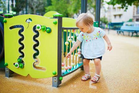 Adorable toddler girl having fun on playground. Outdoor activities for kids Foto de archivo