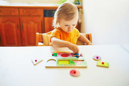 Adorable toddler girl doing wooden puzzle. Child learning geometric shapes. Kid learning to solve problems and developing cognitive skills