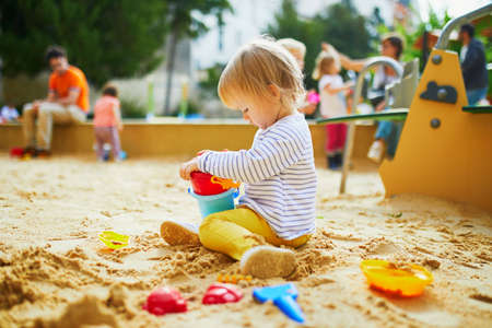 Adorable little girl on playground in sandpit. Toddler playing with sand molds and making mudpies. Outdoor creative activities for kids Reklamní fotografie