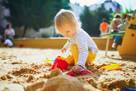 Adorable little girl on playground in sandpit. Toddler playing with sand molds and making mudpies. Outdoor creative activities for kids Standard-Bild