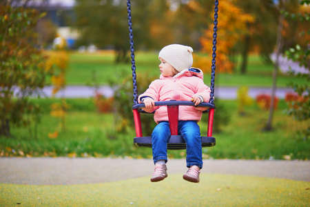Adorable little girl on the playground. Toddler having fun on a swing on a fall day. Outdoor activities for small kids Stock Photo