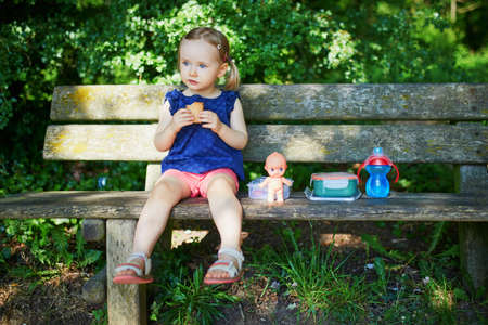 Adorable toddler girl sitting on the bench and having picnic on a summer day. Child enjoying healthy snack in park. Outdoor summer activity for small kids