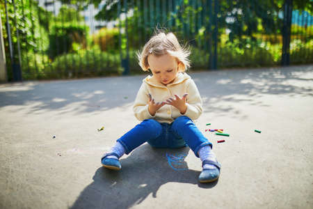 Adorable toddler girl at her dirty hands after drawing with colorful chalks on asphalt. Outdoor activity and creative games for small kids