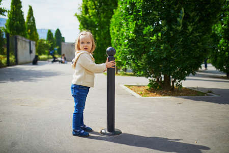 Adorable toddler girl walking on a city street. Child playing with roadside barriere post outdoors on a summer day. Outdoor activity for kids