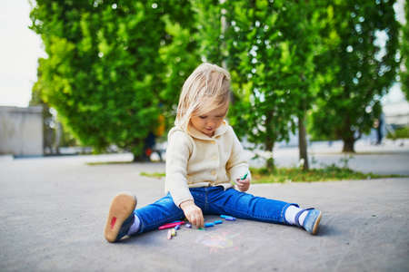 Adorable toddler girl drawing with colorful chalks on asphalt. Outdoor activity and creative games for small kids