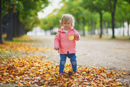 Adorable cheerful toddler girl running in Tuileries garden in Paris, France. Happy child enjoying warm and sunny fall day. Outdoor autumn activities for kids Фото со стока