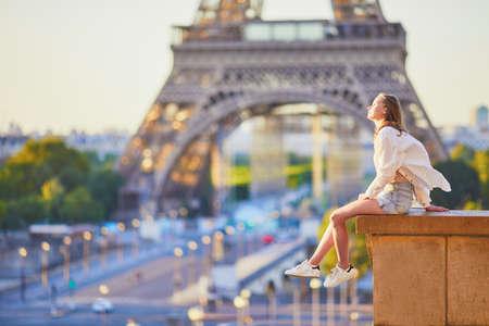 Piękna młoda dziewczyna siedzi w pobliżu wieży Eiffla w Paryżu. Turystka ciesząca się wakacjami we Francji Zdjęcie Seryjne
