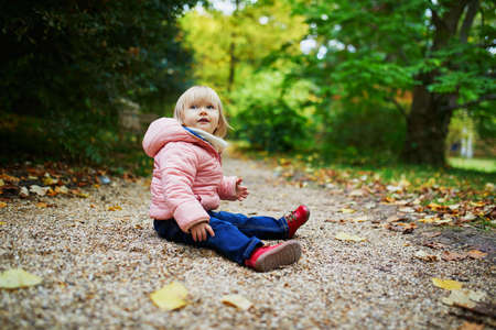 Adorable cheerful toddler girl in autumn park in Paris, France. Happy child enjoying warm and sunny fall day. Outdoor autumn activities for kids Фото со стока