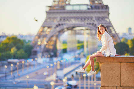 Beautiful young girl sitting near the Eiffel tower in Paris. Tourist enjoying her vacation in France