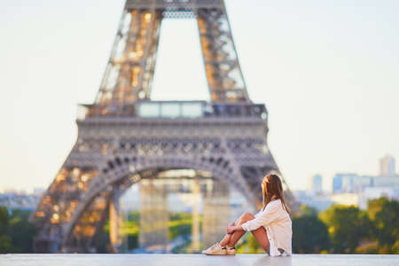 Beautiful young girl sitting near the Eiffel tower in Paris. Tourist enjoying her vacation in France Stock Photo