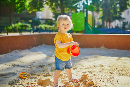 Adorable little girl having fun on playground in sandpit. Toddler playing with sand molds and making mudpies. Outdoor creative activities for kids Stock Photo