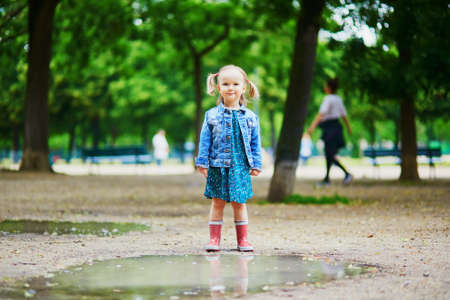 Child wearing red rain boots and jumping in puddle on a summer day. Adorable toddler girl having fun with water and mud in park on a rainy day. Outdoor activities for kids